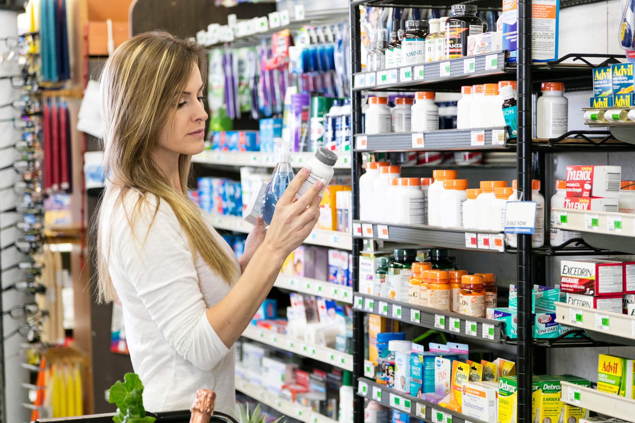 woman in drug store looking at vitamin label