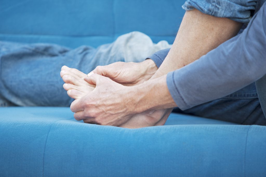 man rubbing sore foot