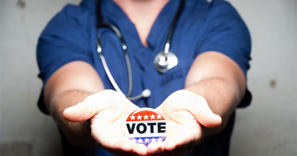 doctor holds vote pin