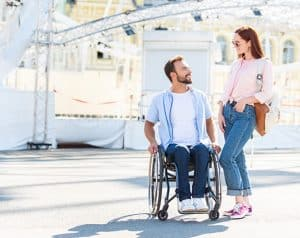 Couple at theme park man in wheelchair